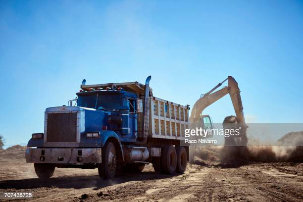 truck near digger in dirt field - ダンプカー ストックフォトと画像