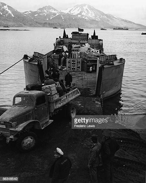 A truck of supplies drives off the back of a landing craft tank docked on the Attu shoreline Aleutian Islands Alaska 1943 American sailors sit in the...