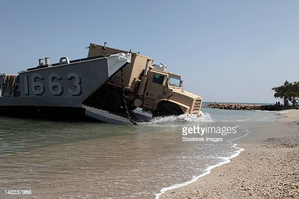 a truck offloads from a landing craft unit. - landing craft stock pictures, royalty-free photos & images