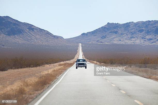 Truck on lonely road in desert