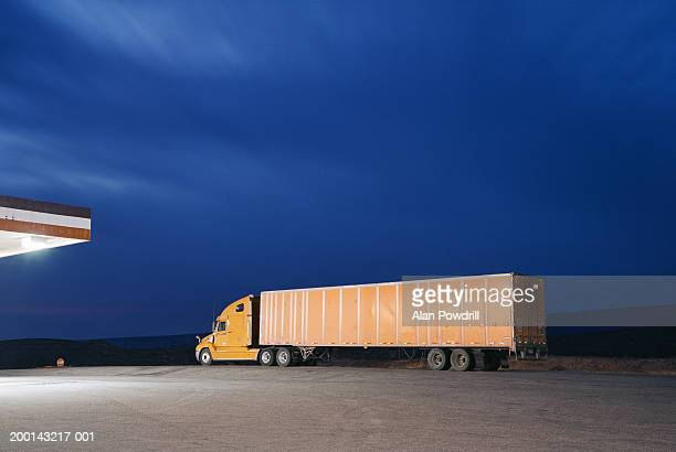 Truck on road by petrol station, dusk
