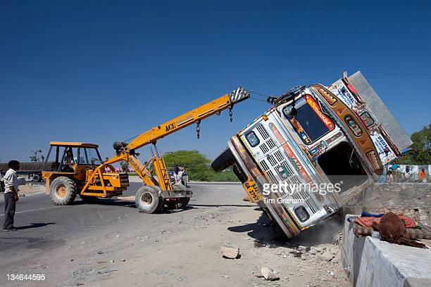 Truck overturned in traffic accident lifted by ACE lifting gear on Delhi to Mumbai National Highway 8 at Jaipur Rajasthan India