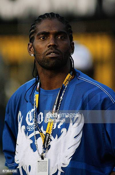 Truck owner and NFL receiver Randy Moss watches action on the track during the NASCAR Camping World Series North Carolina Education Lottery 200 on...