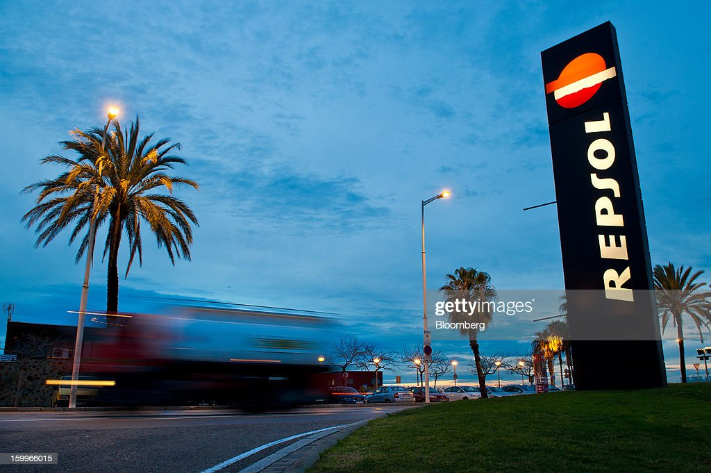 A truck passes an illuminated sign outside a Repsol SA gas station near La Marbella beach in Barcelona, Spain, on Wednesday, Jan. 23, 2013. Repsol SA, Spain's largest energy company, expects to sell liquefied natural gas assets for about 2 billion euros ($2.7 billion) by early February, according to a person familiar with the matter. Photographer: David Ramos/Bloomberg via Getty Images