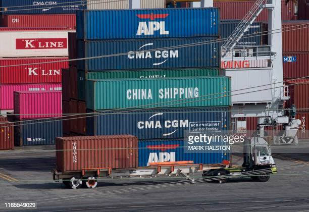 A truck passes by shipping containers at the Port of Los Angeles after new tariffs on Chinese imports was imposed by President Trump in Long Beach...