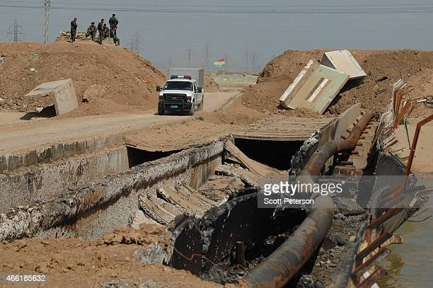 A truck passes destroyed sections of bridge over a canal as Iraqi Kurdish forces push the frontline forward against ISIS forces in the Tal alWard...