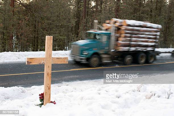 A truck passes where a cross has been erected and roses placed at its base along the side of Highway 395 where LaVoy Finicum was shot and killed by...