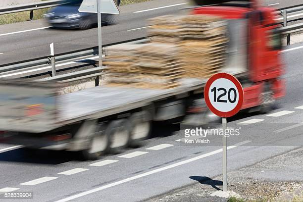 Truck passing 120 kilometer per hour speed limit sign on motorway, Spain