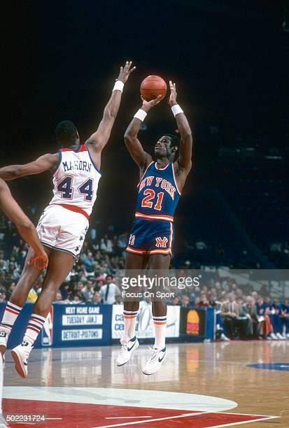 Truck Robinson of the New York Knicks shoots over Rick Mahorn of the Washington Bullets during an NBA basketball game circa 1984 at the Capital...