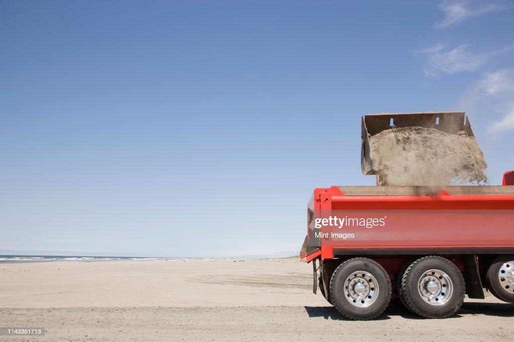 Truck shoveling sand on beach : Stock Photo