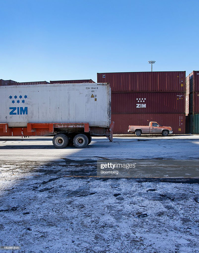 A truck sits next to ZIM Integrated Shipping Services Ltd. freight containers stacked at the Port Of Halifax's South End container terminal, operated by Halterm Ltd., in Halifax, Nova Scotia, Canada, on Tuesday, Jan. 29, 2013. Statistics Canada (STCA) is scheduled to release gross domestic product data on Jan. 31. Photographer: Aaron McKenzie Fraser/Bloomberg via Getty Images