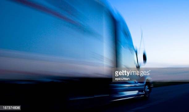 Truck speeding down the freeway at dusk