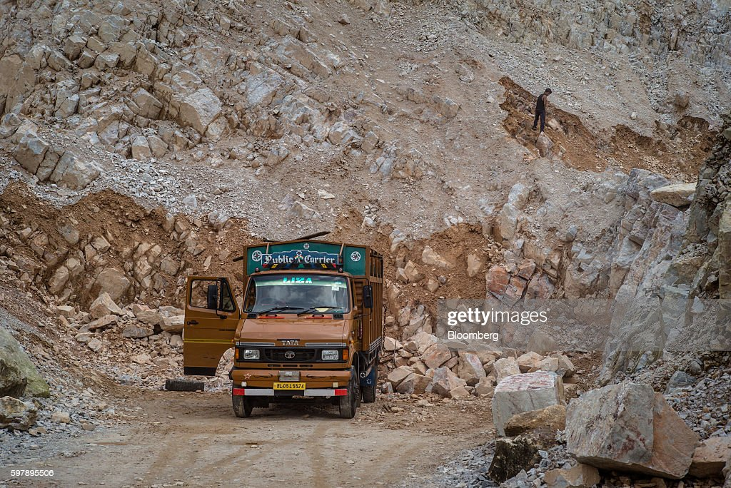 A truck stands parked as a daily wage laborer works at a