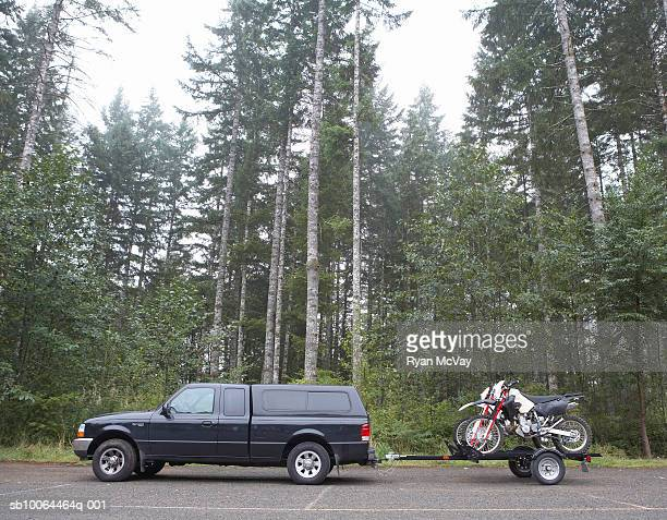Truck towing motorbikes on trailer in forest, side view