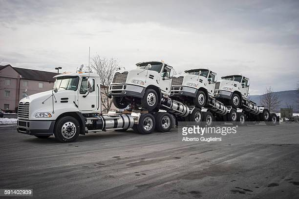 Truck towing truck engines on dirt road