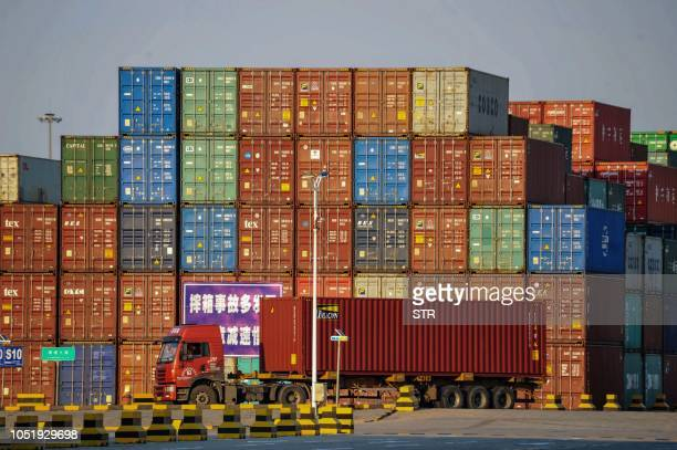 A truck transports a container next to stacked containers at a port in Qingdao in China's eastern Shandong province on October 12 2018 China's trade...