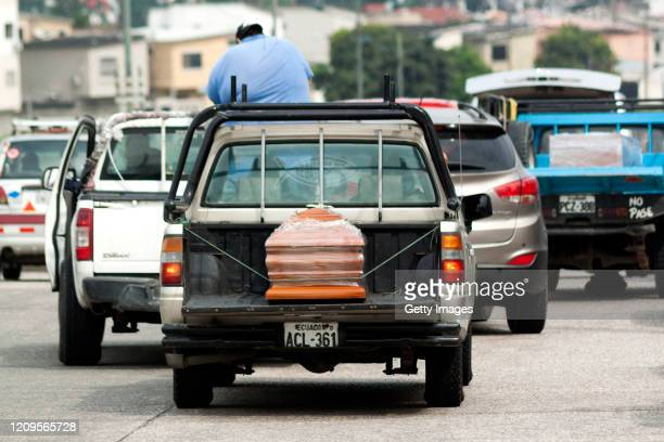 Truck transports a wooden casket wrapped in plastic to enter to the cemetery on April 9, 2020 in Guayaquil, Ecuador. Emergency Operations Committee...