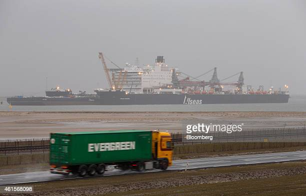 A truck transports an Evergreen Marine Corp shipping container as the Pieter Schelte the world's largest oil rig platform installation...