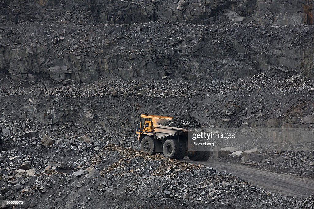 A truck transports excavated rock from the open pit of the Lebedinsky GOK (LGOK) iron ore mining and processing plant, operated by Metalloinvest Holding Co., in Gubkin, Russia, on Tuesday, May 28, 2013. Lebedinsky, Russia's third biggest iron ore mine, is owned 81 percent owned by Russian billionaire Alisher Usmanov, who also owns Mikhailovsky GOK, Russia's second-biggest iron ore mine, and Oskol Electrometallurgical Combine, a steel plant supplied by Lebedinsky. Photographer: Andrey Rudakov/Bloomberg via Getty Images