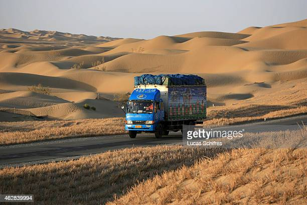 A truck uses the Desert highway to cross the Taklamakan desert on October 12 2006 in Xinjiang province China The Taklamakan Desert is a desert in...