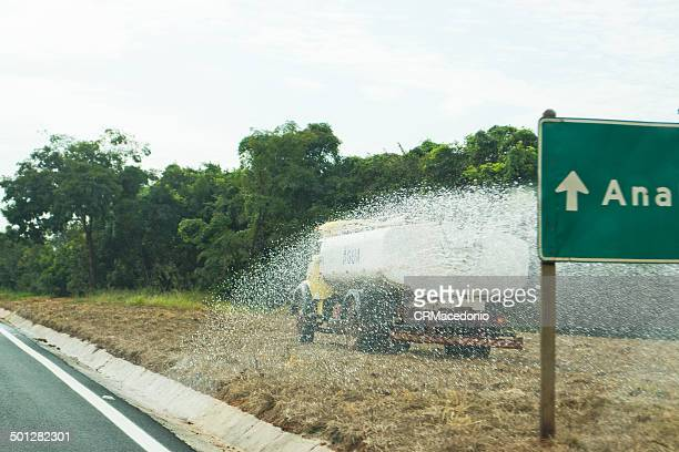 truck watering the dry grass - crmacedonio stock photos and pictures