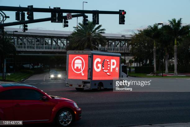 Truck with the letters GQP, a reference to QAnon believers within the GOP, drives outside the Conservative Political Action Conference in Orlando,...