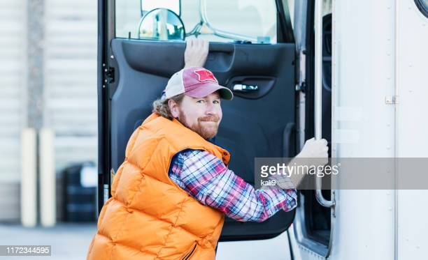 trucker driver climbing into his semi-truck - trucker's hat stock pictures, royalty-free photos & images