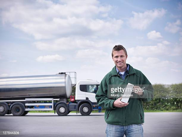 Trucker holding goat's milk by tanker