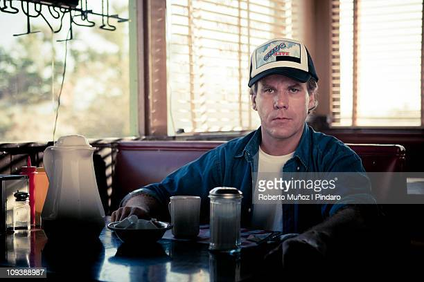 trucker is stares a camera - diner stock pictures, royalty-free photos & images