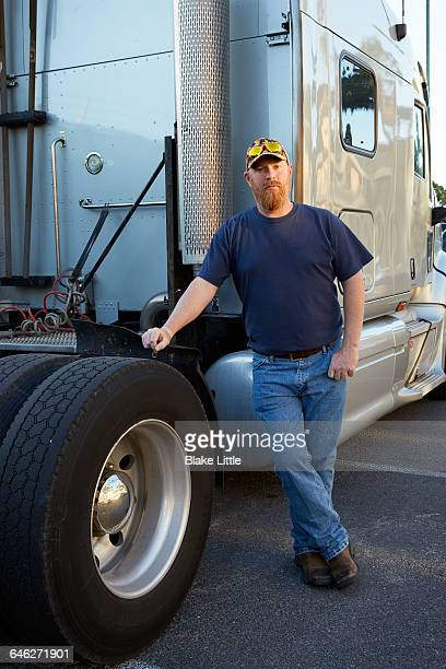 Trucker Portrait leaning on Tire