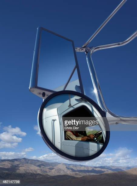 trucker reflected in side mirror - side view mirror stock photos and pictures