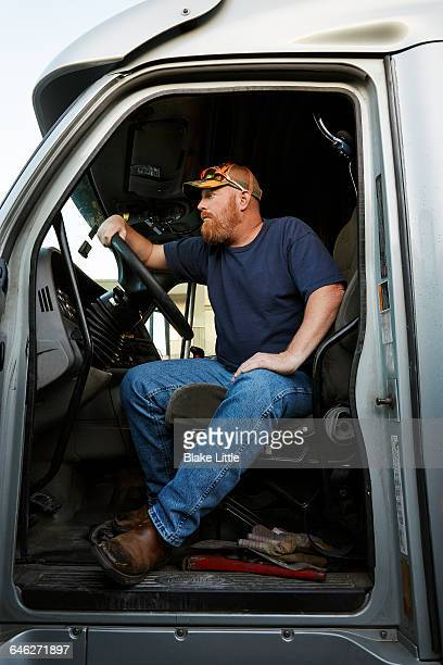 Trucker sitting in truck cab, profile