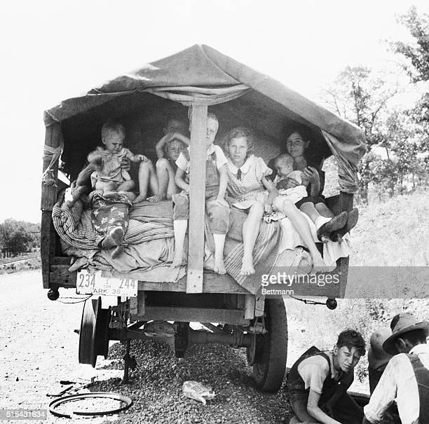 A truckload of Dust Bowl refugees wait for a flat on their truck to be fixed | Location Weber Falls Oklahoma USA
