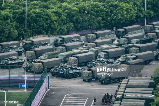 Trucks and armoured personnel vehicles park outside the Shenzhen Bay stadium on August 16 2019 in Shenzhen China Prodemocracy protesters have...