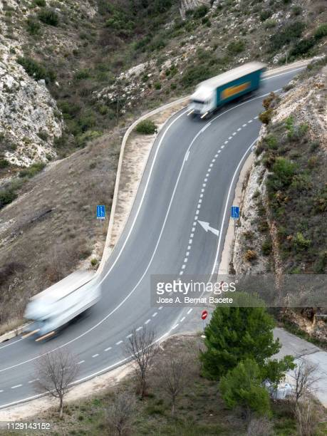 trucks and cars in movement circulating along a road with curves. - transportation occupation stock pictures, royalty-free photos & images