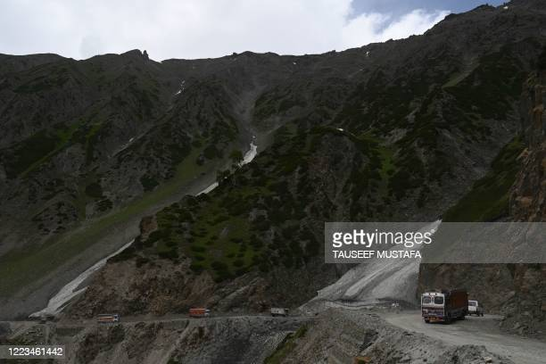 Trucks and fuel tankers drive along the Zojila mountain pass along the Srinagar-Leh Highway some 100 kms from Srinagar on June 29,2020.