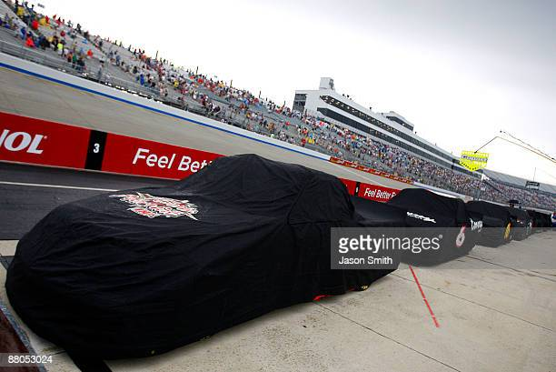 Trucks are covered up on the grid due to a rain delay in the NASCAR Camping World Truck Series AAA Insurance 200 at Dover International Speedway on...