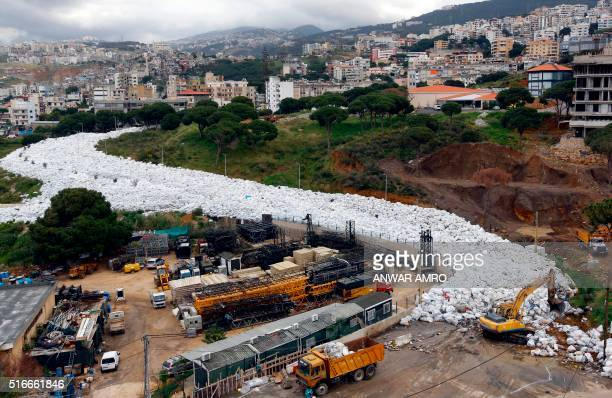 Trucks are seen next to piles of garbage in Jdeideh a Beirut suburb ahead of moving it to the country's largest landfill of Naameh just south of the...