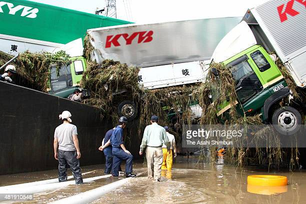 Trucks are seen slipping down to the road due to the heavy rain triggered landslide on July 16 2010 in Kani Gifu Japan