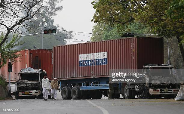 Trucks burned during a protest staged by JamaateIslami supporters against the execution of Mumtaz Qadri former police bodyguard who shot dead...