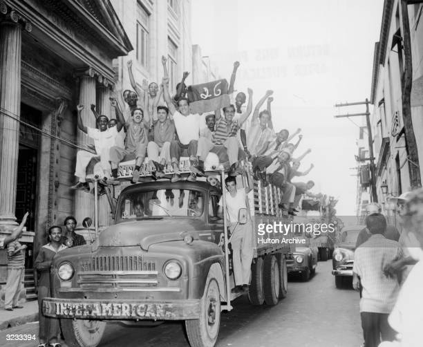 Trucks carry crowds celebrating the removal of dictator Fulgencio Batista and the arrival of Fidel Castro's 'July 26th Movement' Havana Cuba