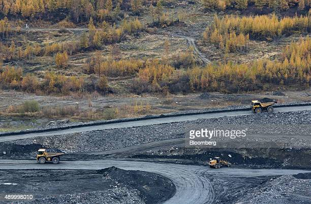Trucks carry rock ore for processing during excavations in the open pit at the Verninsky GOK gold mine and processing plant operated by Polyus Gold...