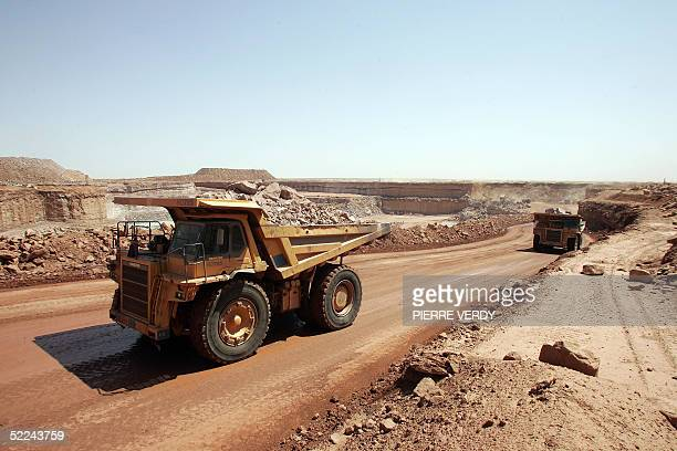 Trucks carry rocks containing uranium 23 February 2005 at the Arlit opencast mine in the Air desert Niger one of the world's most impoverished...
