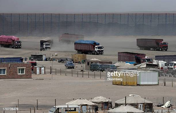 Trucks carrying coal drive in front of a reloading facility on the border with China in South Gobi Mongolia on Thursday June 6 2013 Mongolia a...