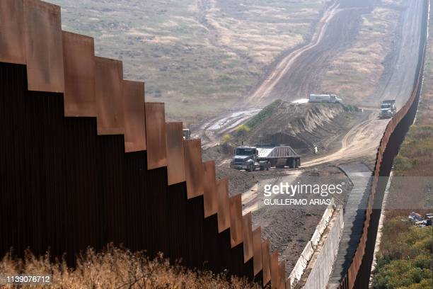 TOPSHOT Trucks carrying construction material ride on the US side of the USMexico border fence as seen from Tijuana in Baja California state Mexico...