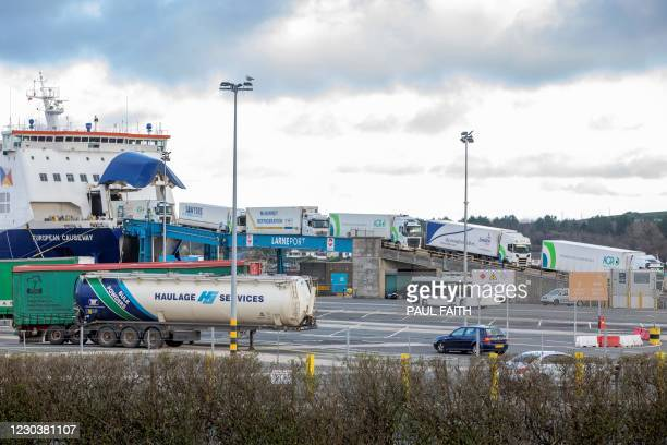 Trucks carrying freight from Scotland disembark a ferry at the Port of Larne in County Antrim, Northern Ireland on January 1 as a new trade border...