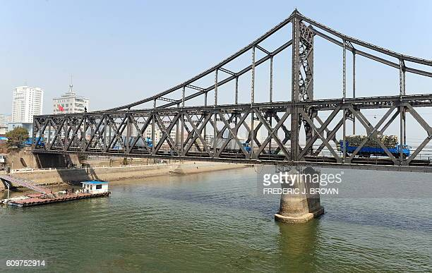 Trucks cross the Sino-Korean Friendship Bridge delivering goods from Dandong, in northeast China's Liaoning province across the Yalu River to the...