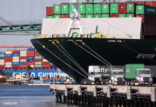 Trucks drive beneath cargo containers stacked on the Ever Lunar container ship at the Port of Los Angeles, the nation's busiest container port, on...