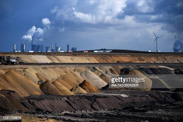 Trucks drive near the coal-fired power station Neurath of German energy giant RWE at the open-cast mine of Garzweiler, western Germany, on March 15,...