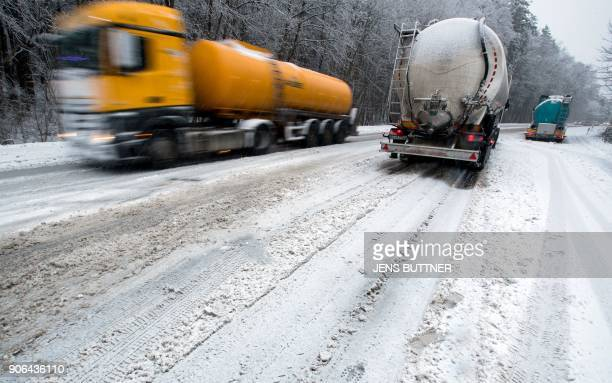 Truck's drive on a snowcovered road near Schwerin eastern Germany on January 18 2018 Weather forecasts predict a heavy storm and snow over Germany /...